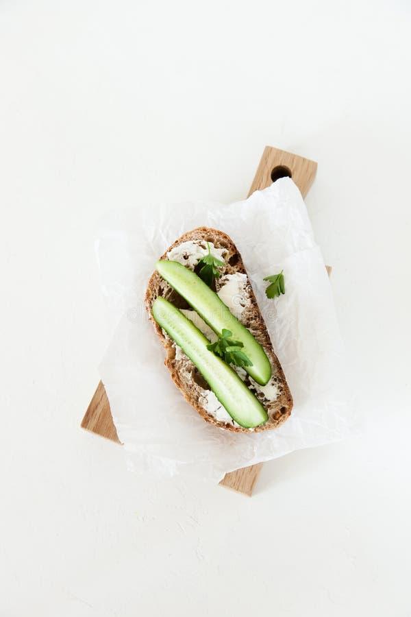 Ett stycke av bröd med smör, saltar med gurkan, och gräsplaner ligger på ett träbräde på en vit bakgrund arkivbilder