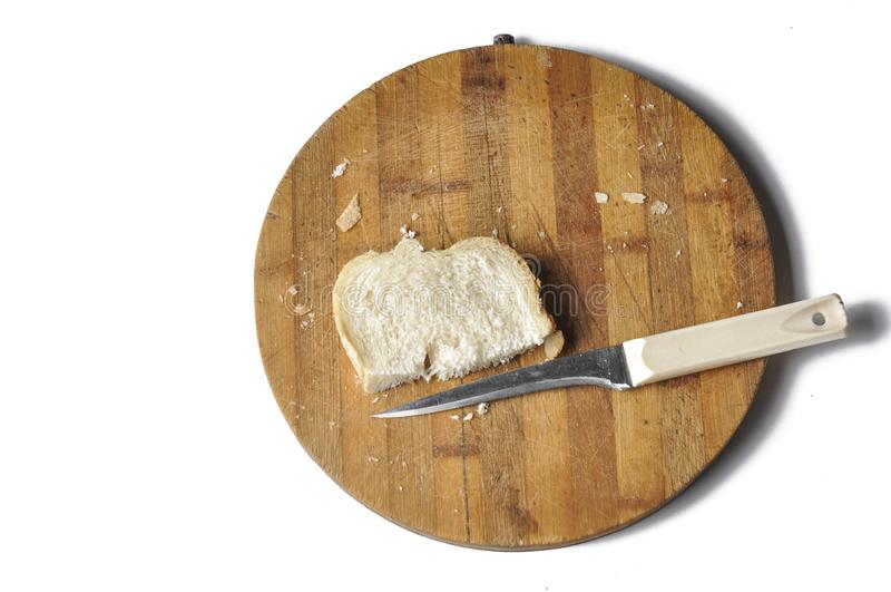 Ett stycke av br?d och en kniv p? ett tr?br?de som isoleras p? en vit bakgrund royaltyfri bild
