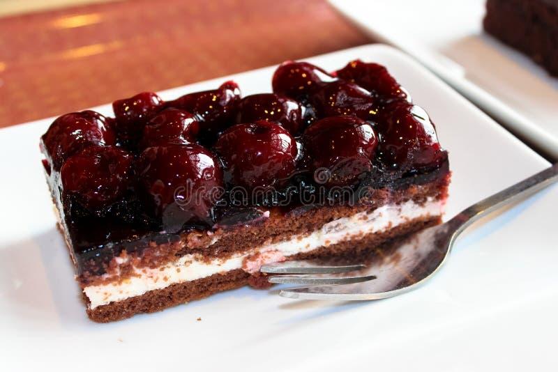 Ett stycke av chokladkakan med körsbär royaltyfria bilder