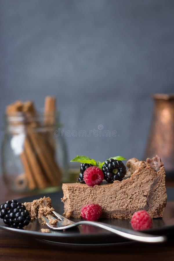 Ett stycke av chokladostkaka med björnbär och hallon arkivbilder