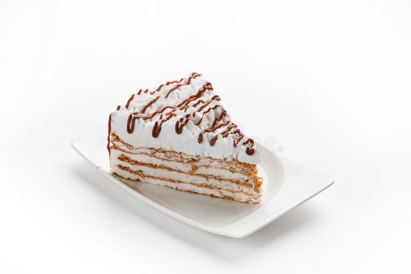 Ett stycke av den piskade kräm- kakan som dekoreras med choklad i en vit rektangulär platta på en isolerad vit bakgrund arkivfoto