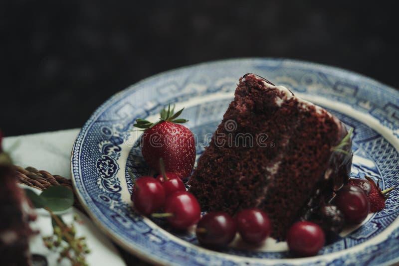 Ett stycke av en chokladkaka med jordgubbar och björnbär arkivfoton