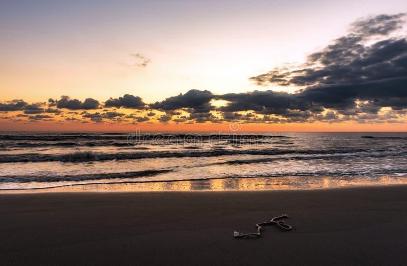 Ett stycke av fiskerepet på stranden på fantastisk färgrik gryning arkivfoton