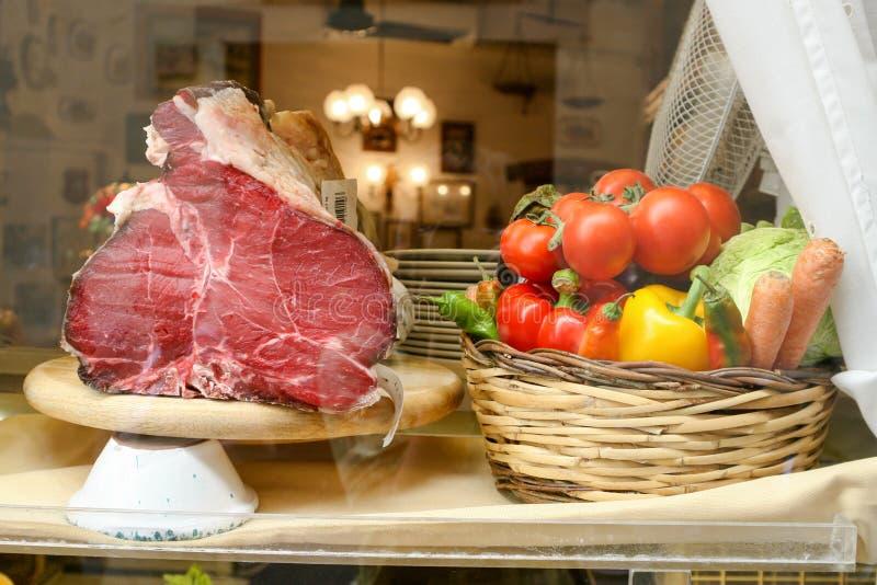 Ett stycke av kött på ställningen Grönsaktomater, spanska peppar, kål, morötter i en korg arkivbild