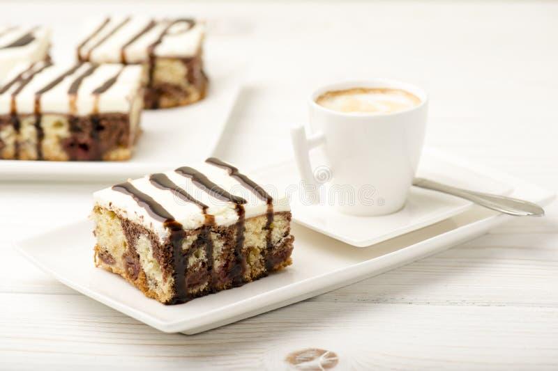 Ett stycke av kakan med körsbäret och choklad och en kopp kaffe på den vita träbakgrunden arkivbild
