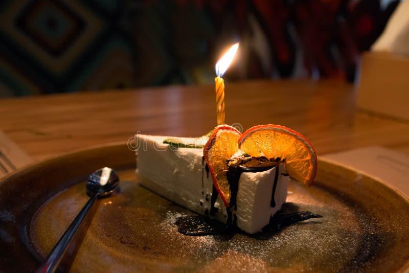 Ett stycke av kakan med stearinljus, för födelsedag med apelsiner arkivfoton