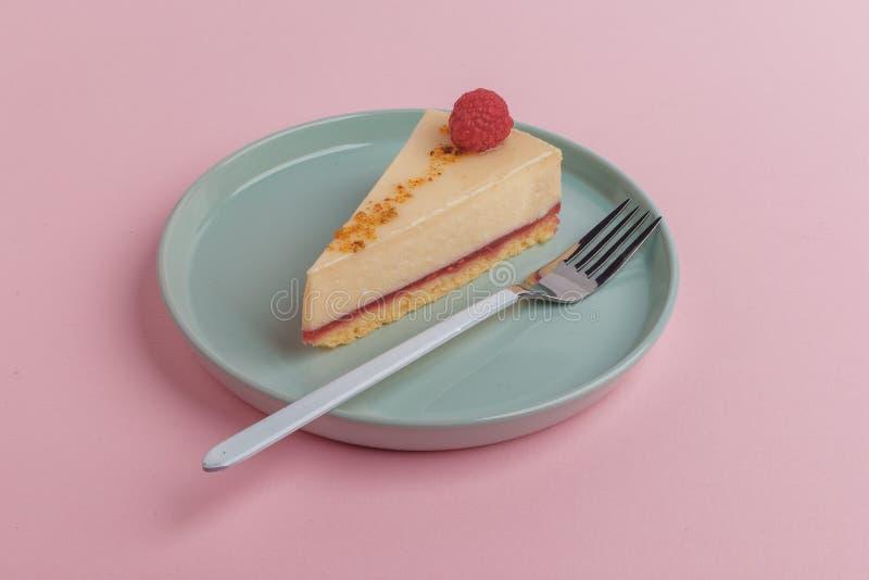 Ett stycke av kakan, ostkaka på en platta med en gaffel på en rosa bakgrund fotografering för bildbyråer
