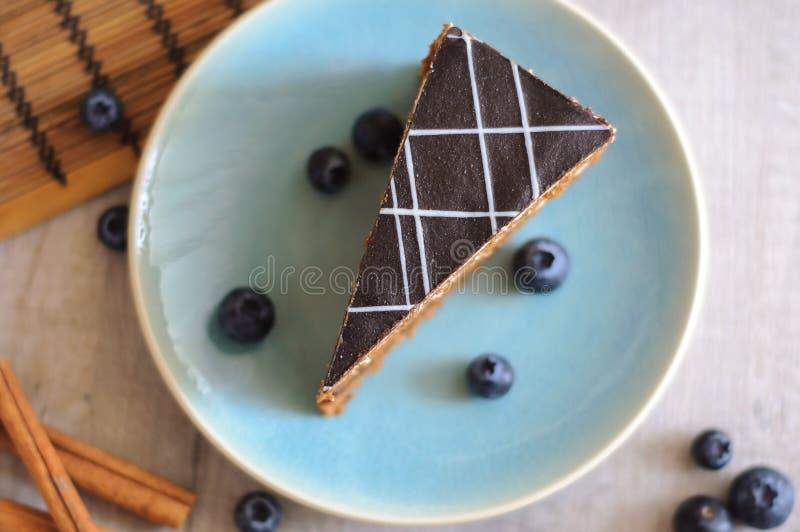 Ett stycke av kakan på en platta, blåbär och kanelbruna pinnar royaltyfri foto
