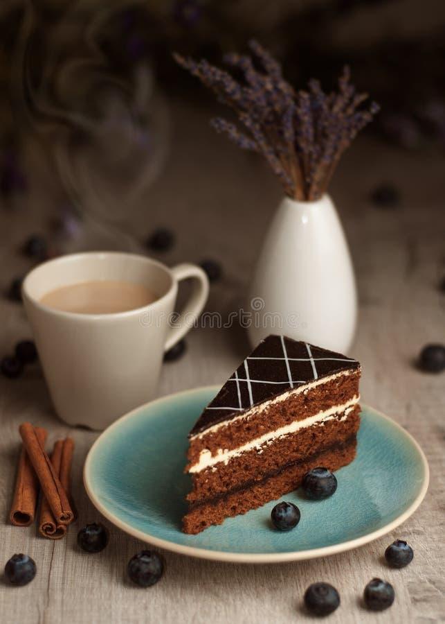 Ett stycke av kakan på en platta och en kopp kaffe royaltyfri fotografi