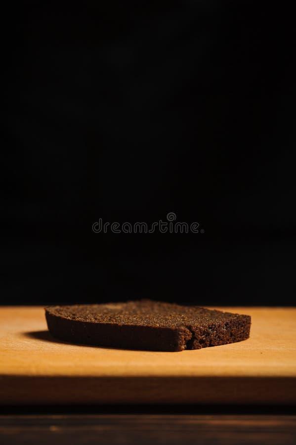 Ett stycke av lögner för svart bröd på en skärbräda royaltyfri fotografi