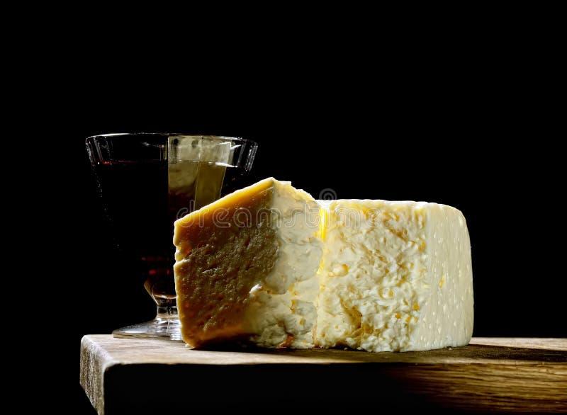 Ett stycke av ost och vin på ett träbräde på en svart bakgrund royaltyfria foton