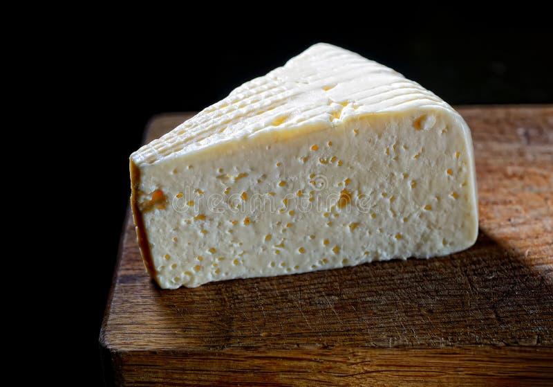 Ett stycke av ost på ett träbräde på en svart bakgrund arkivfoto