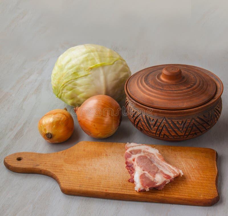 Ett stycke av rått griskött på en skärbräda- och tappninglerakruka och fotografering för bildbyråer
