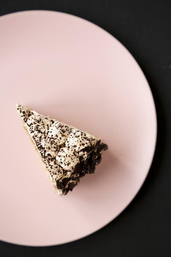 Ett stycke av tiramisukakan på en rosa platta över svart bakgrund, bästa sikt Lekmanna- l?genhet, ?ver huvudet, fr?n ?ver arkivfoton