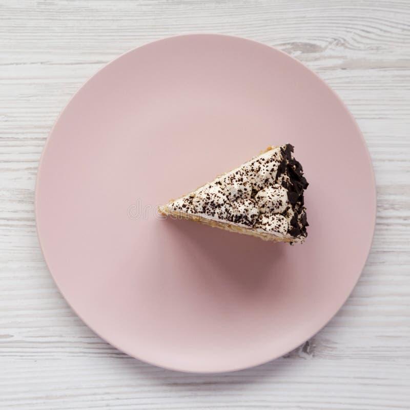 Ett stycke av tiramisukakan på en rosa platta på en vit träbakgrund, bästa sikt Lekmanna- l?genhet, ?ver huvudet, fr?n ?ver arkivbilder