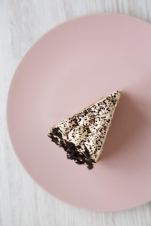 Ett stycke av tiramisukakan på en rosa platta på en vit träbakgrund, bästa sikt N?rbild royaltyfria bilder