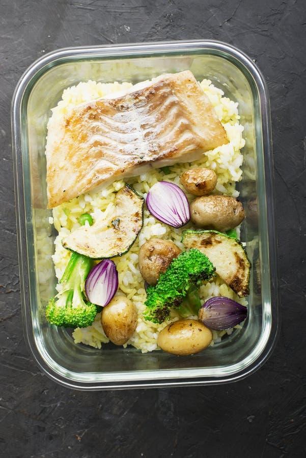 Ett sunt mål för ett mellanmål är en lunchask Glass behållare med den nya ångahavsfisken, ris med gurkmeja som är ny royaltyfria bilder