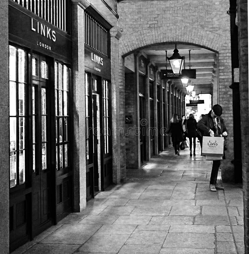 Ett svartvitt skott av manliga sammanlänkningar för en shoppareyttersida av den London Covent trädgården, London UK fotografering för bildbyråer