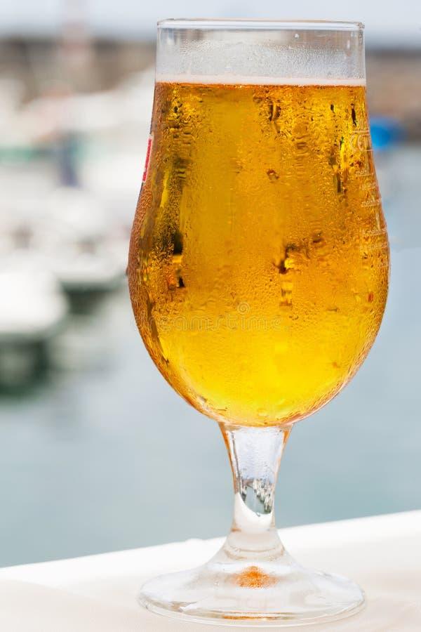 Ett svettigt exponeringsglas av kallt öl på bakgrunden av marina och yachterna i porten arkivfoto