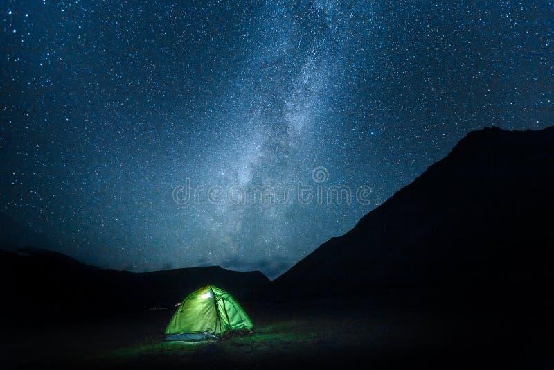 Ett tält glöder under en natthimmel mjölkaktiga Maj mycket av stjärnor Elbrus N arkivbild