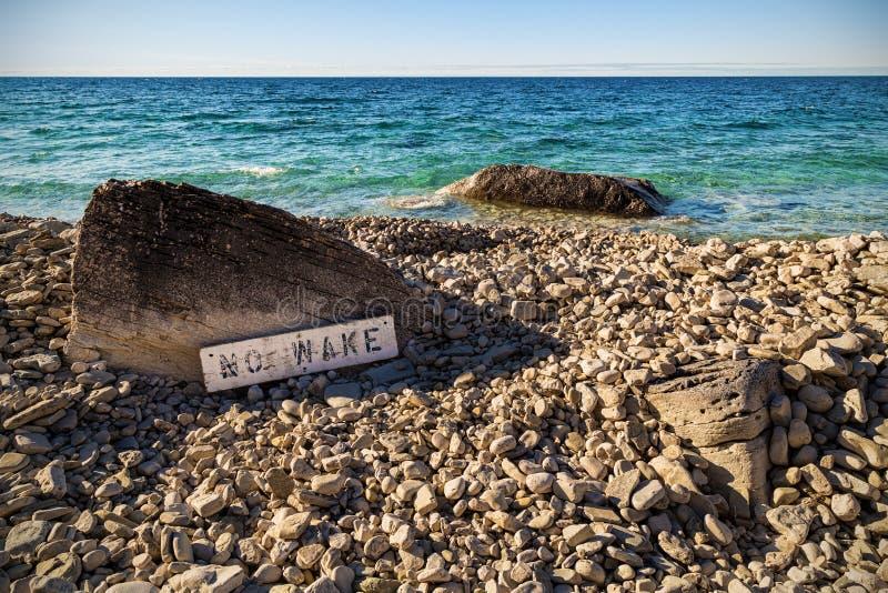 Ett tecken 'för ingen vak 'på en stenig strand i Ontario arkivbild