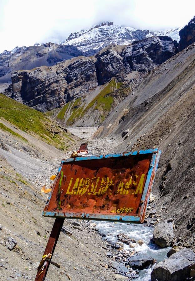 Ett tecken för jordskredområdesvarning ovanför stupat vaggar royaltyfria foton