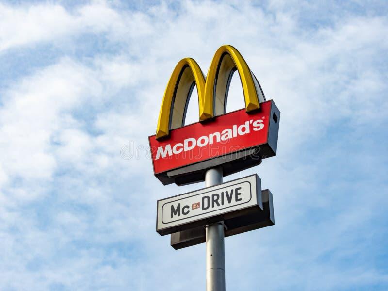 Ett tecken för McDonald ` s McDrive mot den blåa himlen royaltyfria foton