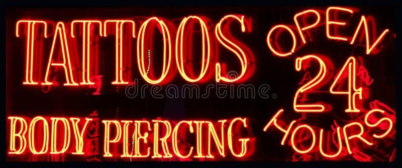 Ett 24 tecken för neon för timmetatueringmottagningsrum royaltyfria bilder