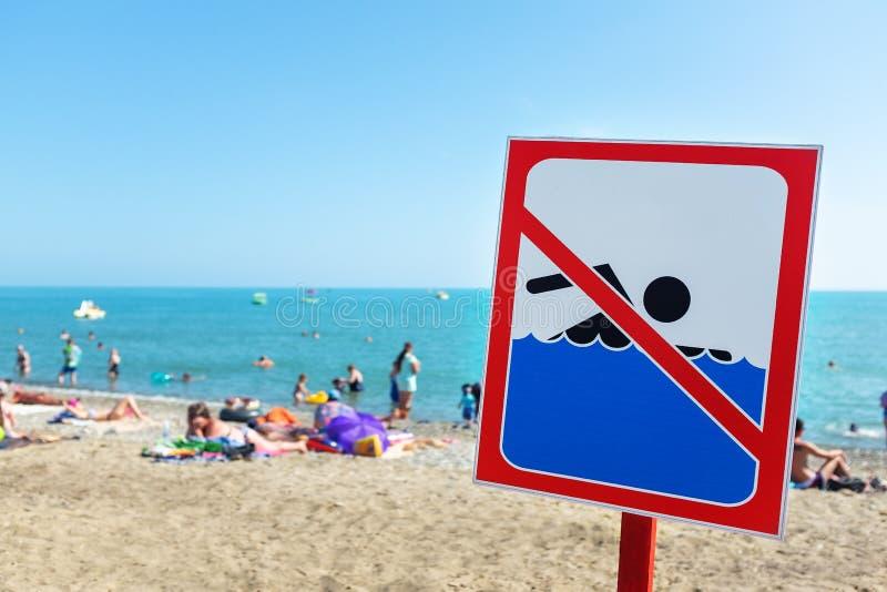 Ett tecken p? stranden l?ts inte simma! Folket badar och vilar p? havet i trots av tecknet och f?rbudet royaltyfri bild