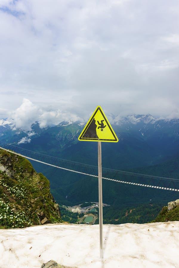 Ett tecken som indikerar faran av att falla från en klippa i bergen arkivfoton