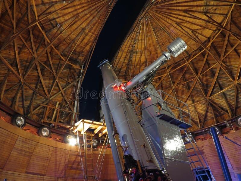 Ett teleskop på Lowell Observatory med en sikt av det Orion's bältet och andra stjärnor som är synliga i himlen ut fönstret royaltyfri fotografi