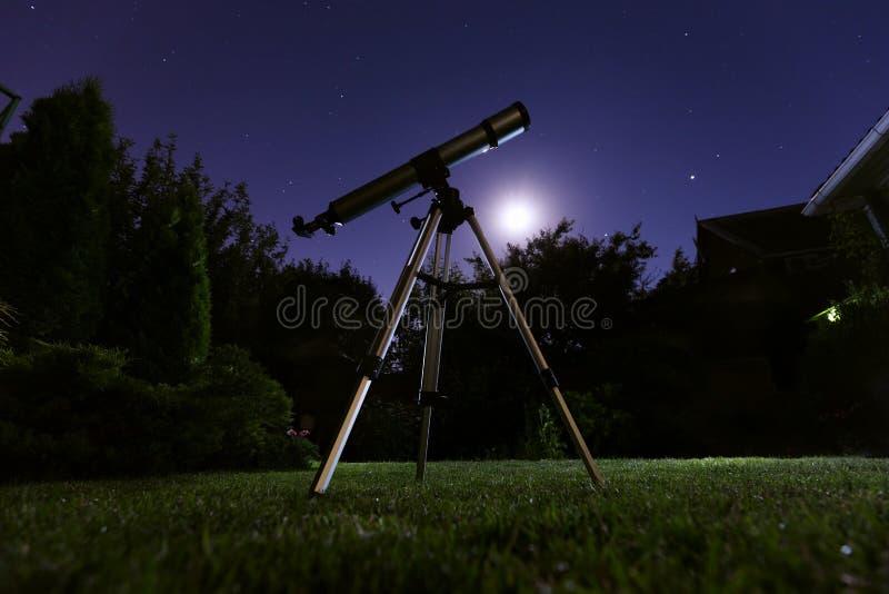 Ett teleskopanseende på trädgården med natthimmel i bakgrunden Astronomi och stjärnor observera begrepp royaltyfri fotografi