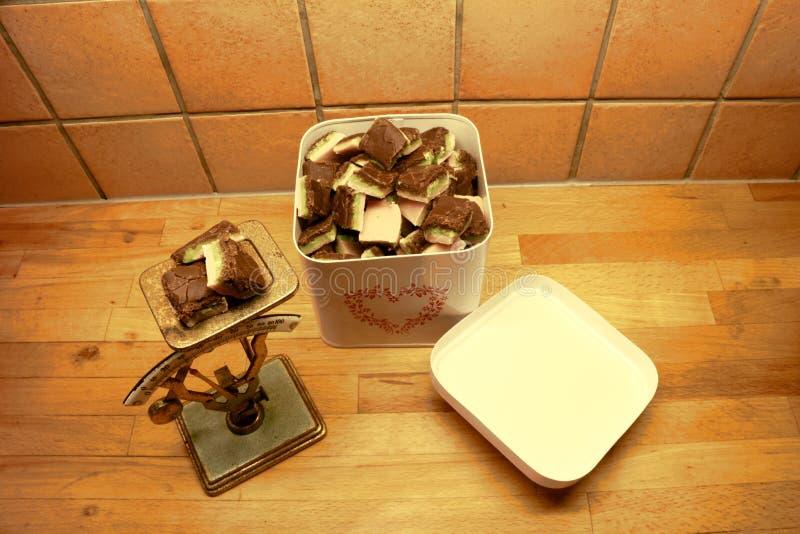 Ett tenn kan fyllt med hemlagad konfekt och en gammal lantlig skala med konfektstycken överst royaltyfria bilder