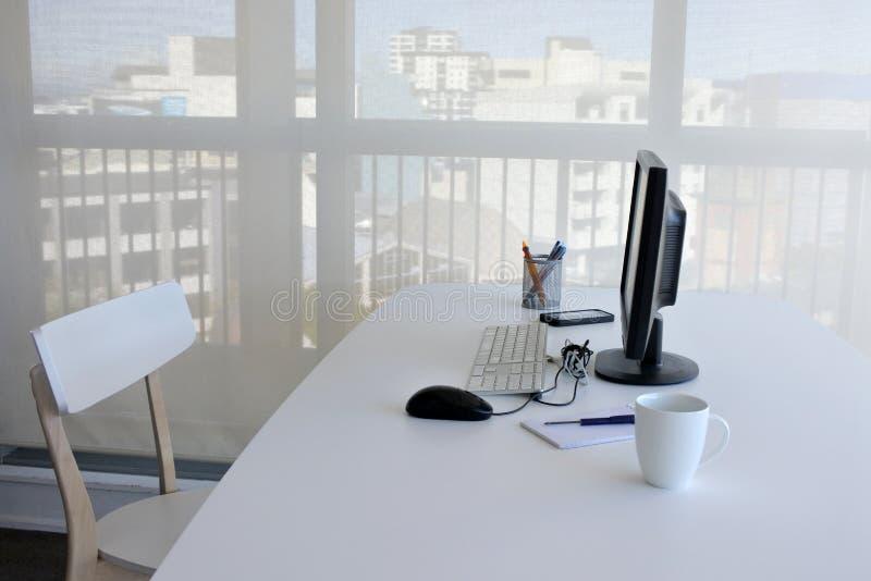 Ett tomt enkelt funktionsdugligt skrivbord i inrikesdepartementet royaltyfri bild
