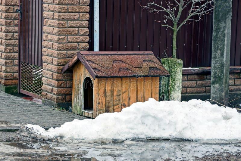 Ett tomt hundskjul nära ett staket i en snödriva royaltyfria bilder