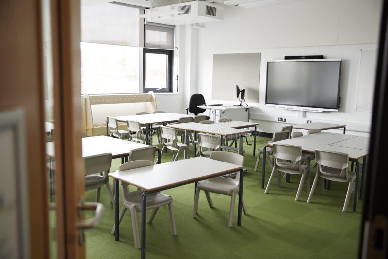 Ett tomt klassrum i en grundskola för barn mellan 5 och 11 år med vita skrivbord och stolar som ses från dörröppningen arkivfoto