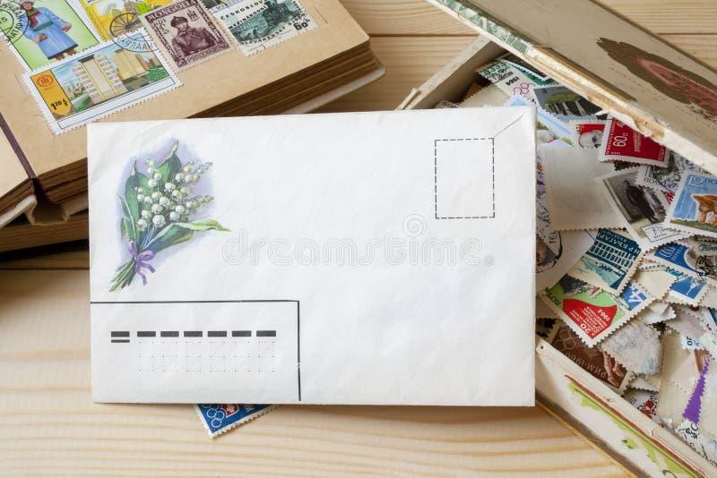 Ett tomt kuvert som framme ligger av en samling av portost?mplar av olika l?nder i den gamla asken och st?mpelh?llaren arkivbild