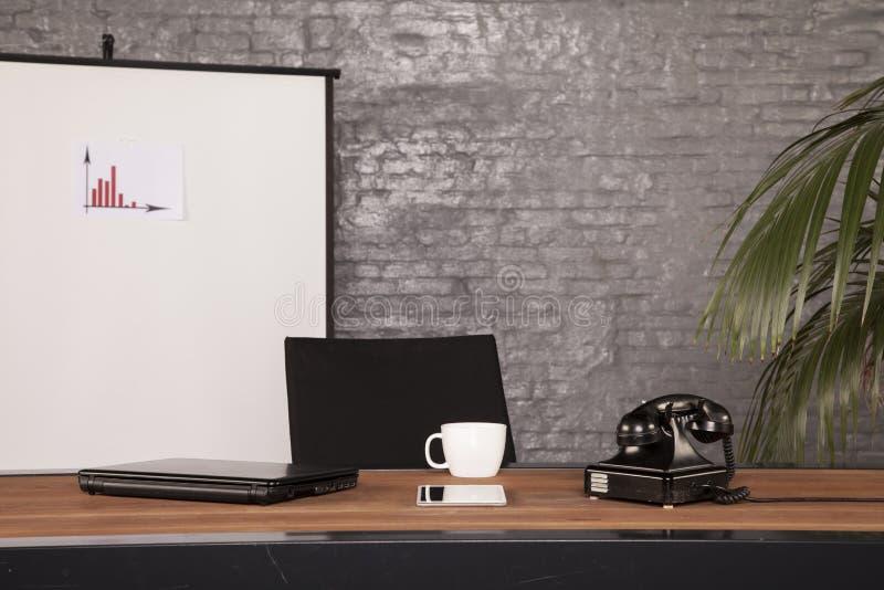 Ett tomt skrivbord i kontoret som väntar på ny anställd arkivbild
