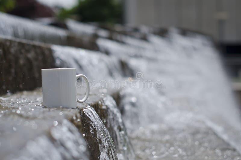 Ett tomt vitt kaffe rånar på den långa vattenspringbrunnen royaltyfria bilder