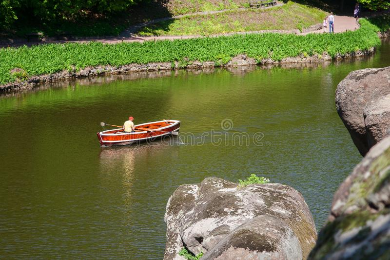 Ett Touristic fartyg på den lugna yttersidan av sjön i Sofiyivsky P arkivbild