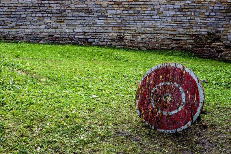 Ett trämål för en armborst med en röd färg med vita cirklar i borggården av en forntida slottslott En grön gräsmatta, arkivbilder