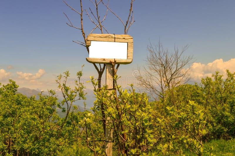 Ett trätecken för riktning för bergslinga med en himmel- och trädbakgrund arkivfoton