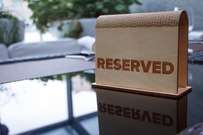 Ett trätecken med inskriften som reserveras på en exponeringsglastabell i en trendig restaurang eller ett kafé, selektiv fokus fotografering för bildbyråer