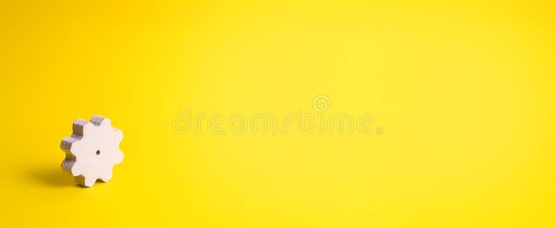 Ett tr?kugghjul p? en gul bakgrund Begreppet av teknologi- och aff?rsprocessar minimalism Mekanism och apparater arbete arkivfoto