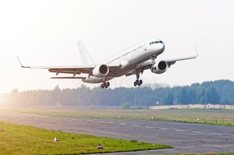Ett transportflygplan tar av från landningsbana i en liten flygplats royaltyfri foto