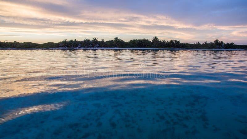 Ett tropiskt hav med en sticka av den vita sand och djungeln royaltyfri bild