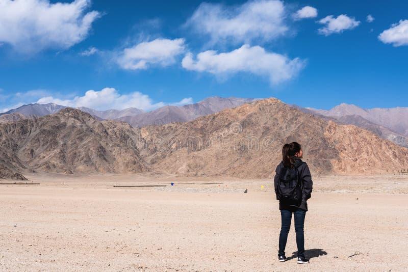Ett turist- anseende för härlig asiatisk kvinna och vänder tillbaka framme av bakgrund för berg och för blå himmel royaltyfri fotografi
