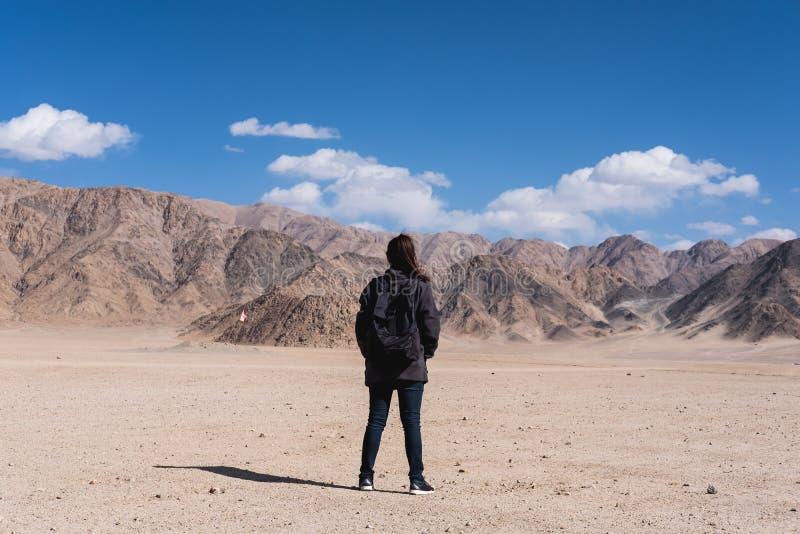 Ett turist- anseende för härlig asiatisk kvinna och vänder tillbaka framme av bakgrund för berg och för blå himmel arkivfoton