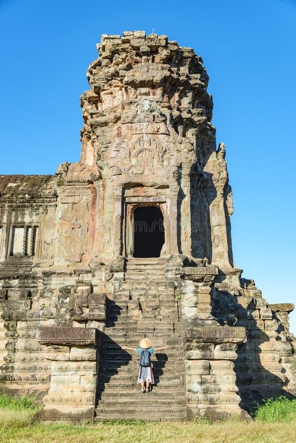 Ett turist- bes?ka Angkor Wat f?rd?rvar p? soluppg?ng, loppdestinationen Cambodja Kvinna med den traditionella hatten och lyftta  royaltyfria foton