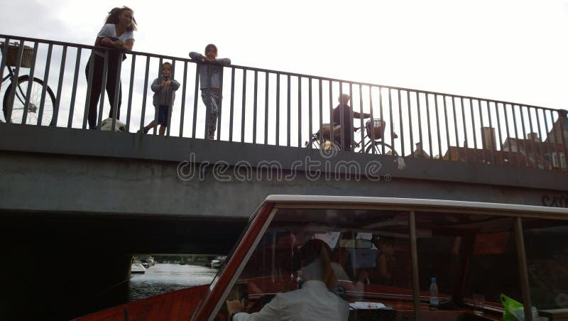 Ett turist- fartyg seglar under bron i Köpenhamn På brofolket som håller ögonen på på kanalen royaltyfria foton